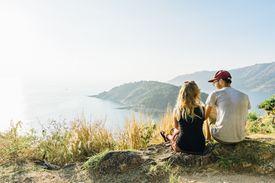 Couple sitting on rocks, overlooking body of water.