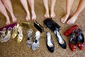 Ladies feet, with shoes and handbags on floor