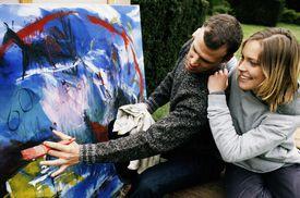 A couple next to a canvas discusses art.