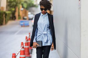 Street style woman in blazer and button down shirt and dark wash jeans