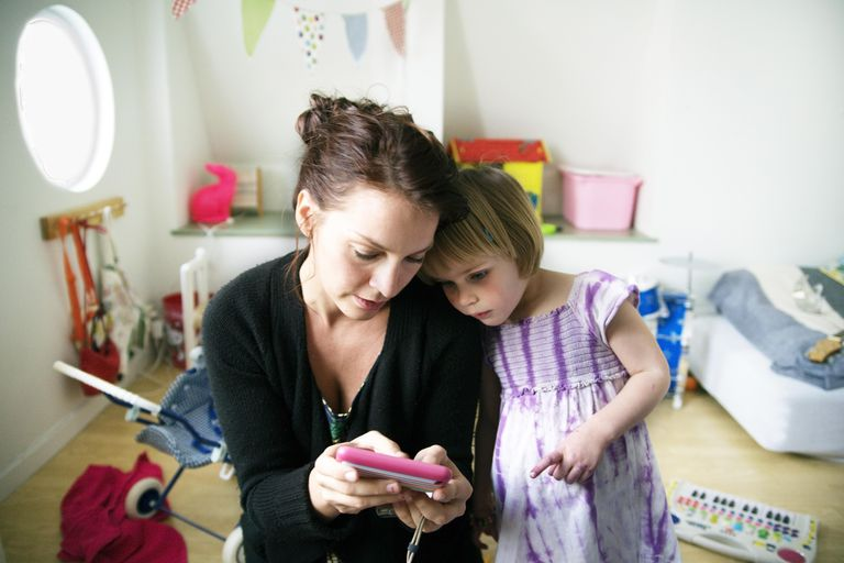 Mother with daughter looking at cell phone