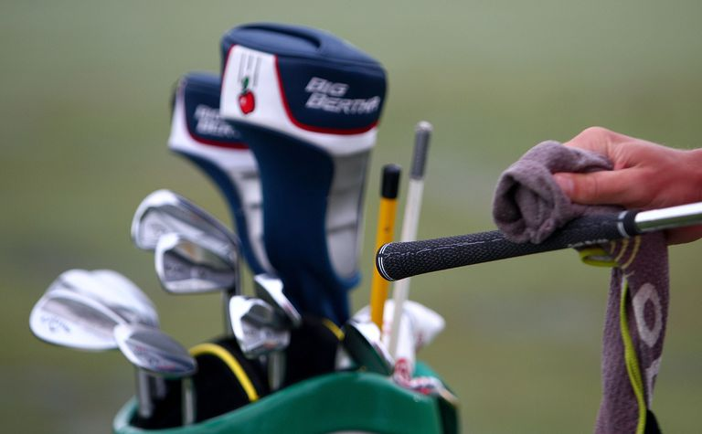A caddie wipes down the grip on a golf club