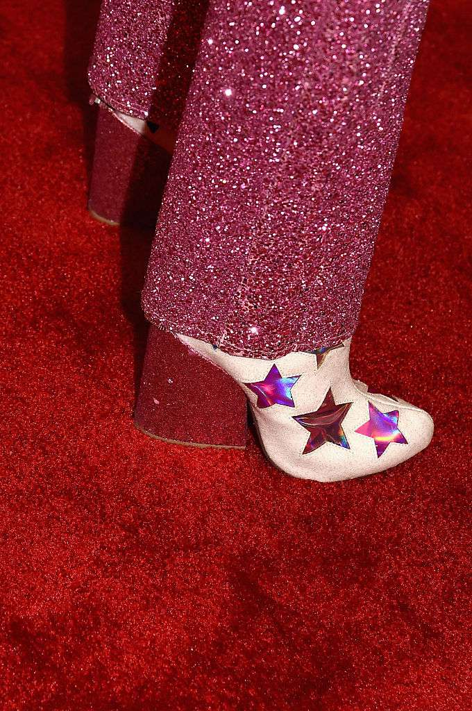 Pink sequin pants and white cowboy boots with pink stars on the red carpet