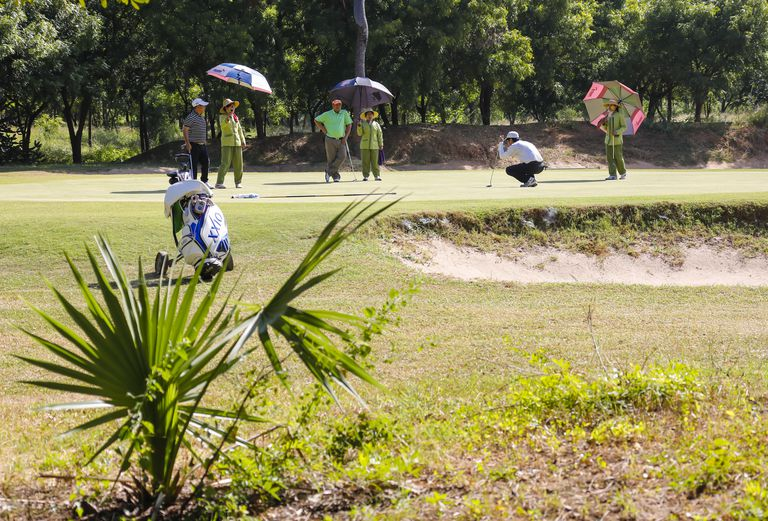 Golfers playing in Myanmar after paying the green fee.