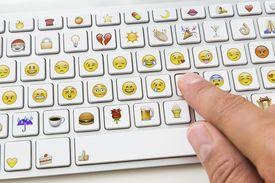 Hand typing on emoticon keyboard