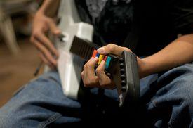 young man playing Guitar Hero