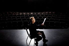 Man holds script in empty theatre