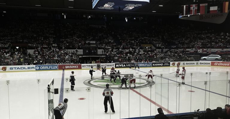 Active hockey game in an arena packed with fans.