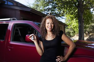 Hispanic woman holding keys to new car