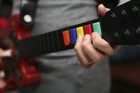 Person holding Guitar Hero controller