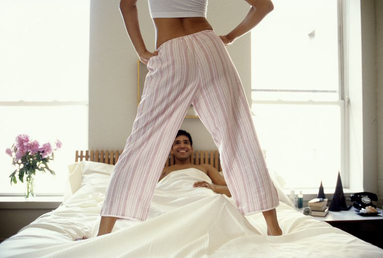 A woman stands over a man in bed.