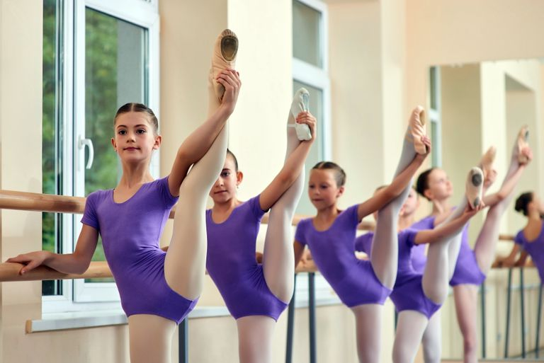 A row of ballerinas in purple practice their leg holds at the ballet barre