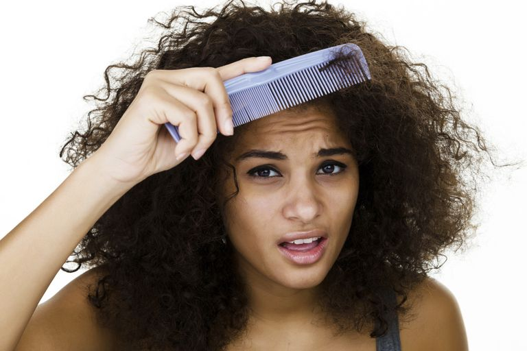 Woman detangling curly natural hair while dry