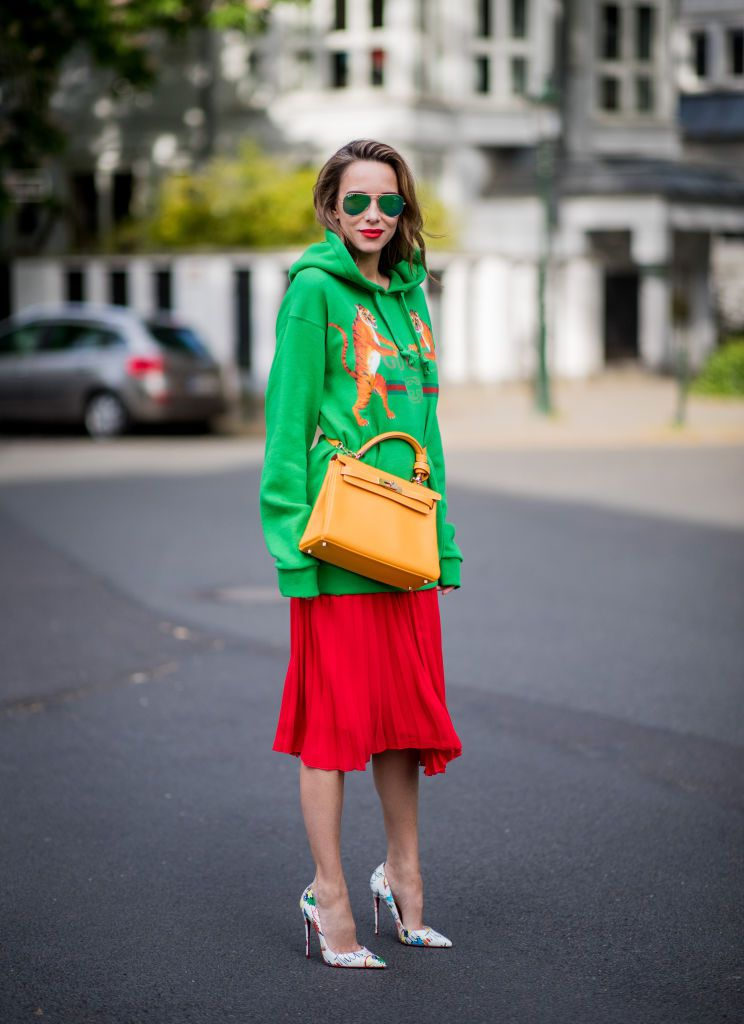 36ad2ceab1 Street style fashion woman wearing a Gucci sweatshirt and pleated skirt