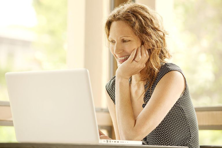 Smiling woman looking at a laptop
