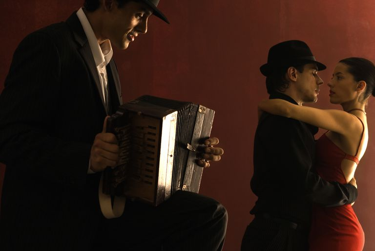 Man playing accordion, couple dancing in background