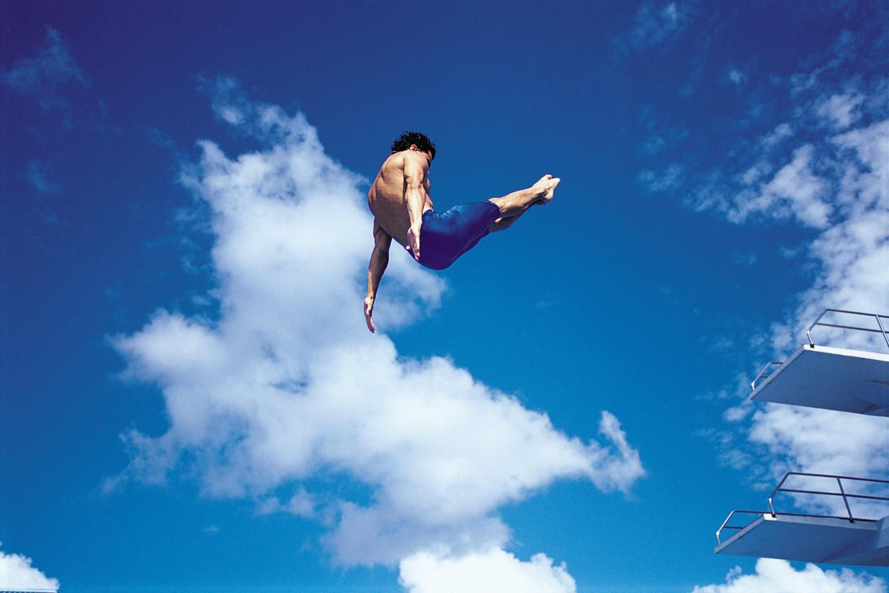 Diver in mid-air against a blue sky.