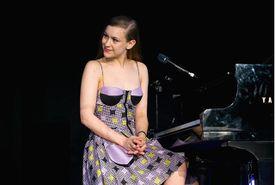 Joanna Newsom sitting at a piano onstage.