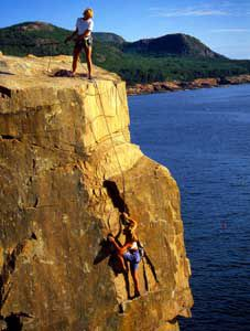 Climbers at Otter Cliff in Acadia National Park, Maine.