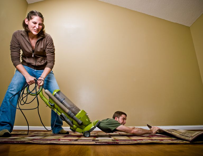 Woman vacuuming and a man being sucked up into the vacuum