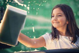 Little girl washing car window, view from inside
