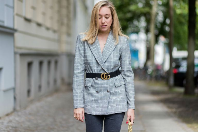 Woman in grey jeans and belted blazer