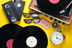 Flat lay retro style attributes, 80s media. Vinyl player, video cassettes, audio cassettes, records, 3d glasses, vintage alarm clock, old books on yellow background. Top view