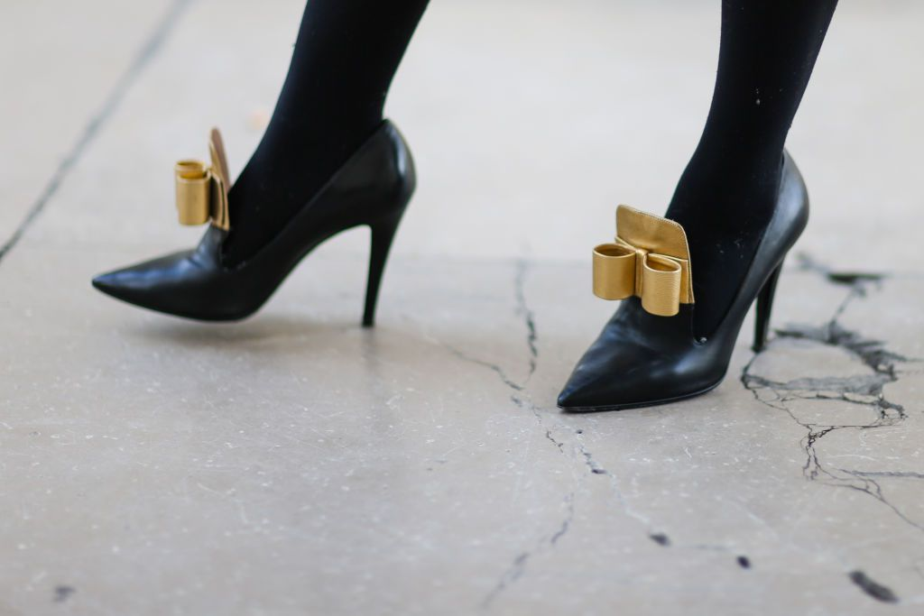 Woman's feet in black pumps with gold bows