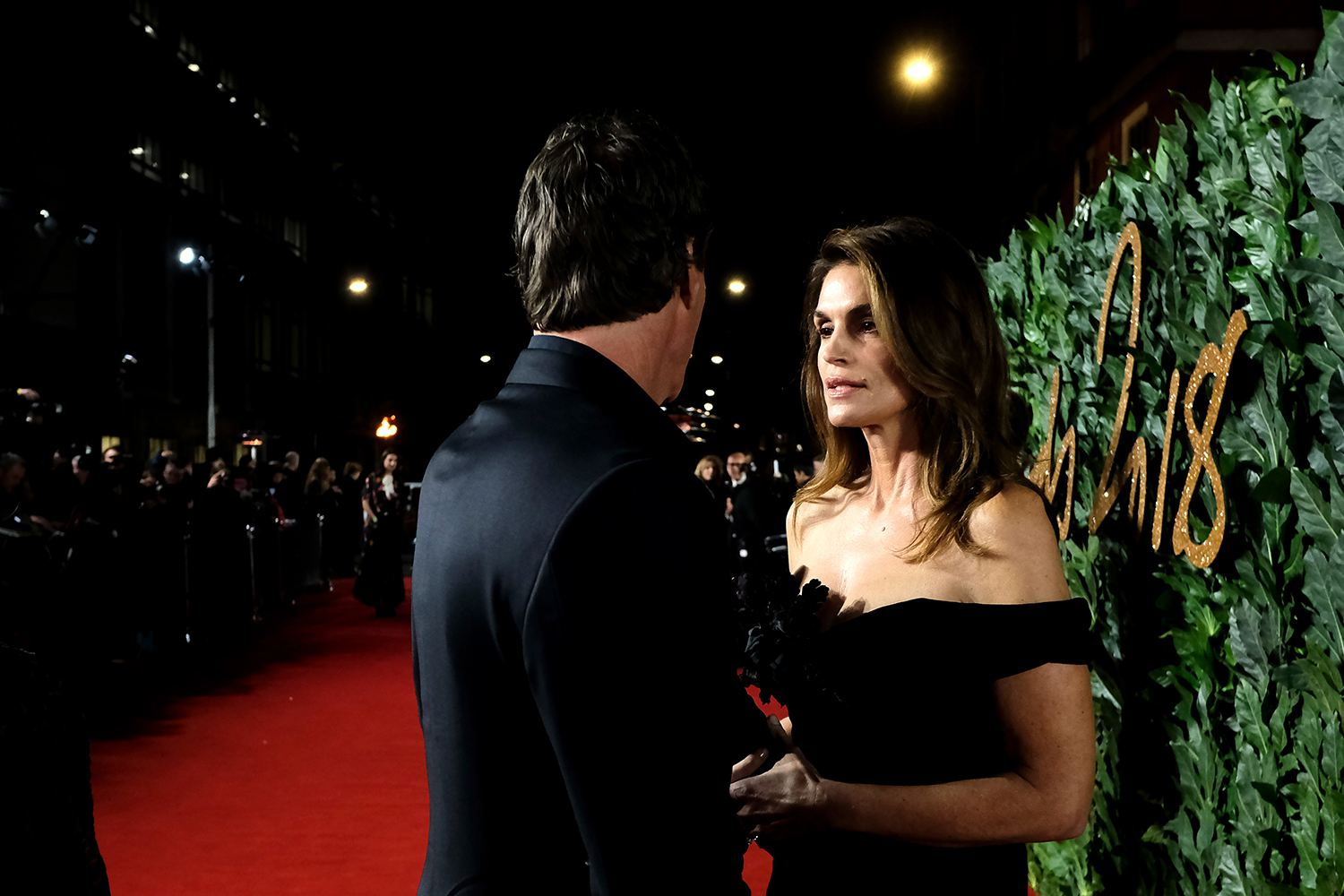 Cindy Crawford having a conversation at a red carpet event.