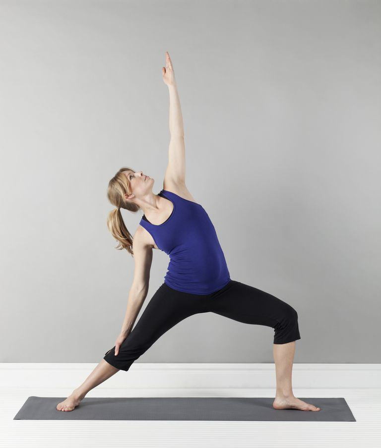 a woman in exercise clothes stretching on a mat
