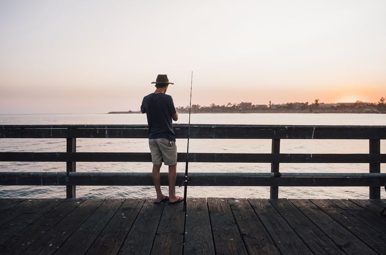 Rear view of man on pier fishing, Goleta, California, United States, North America