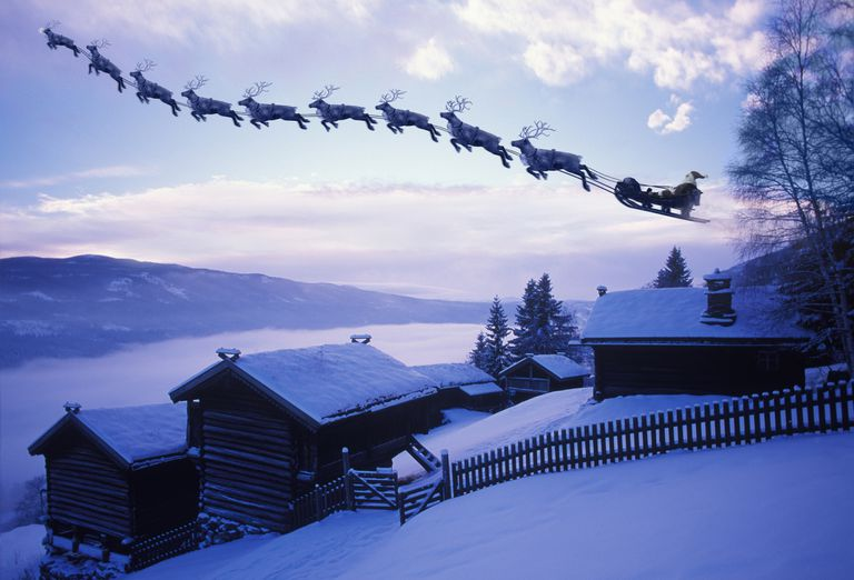 Santa Claus with reindeer flying above a farm -