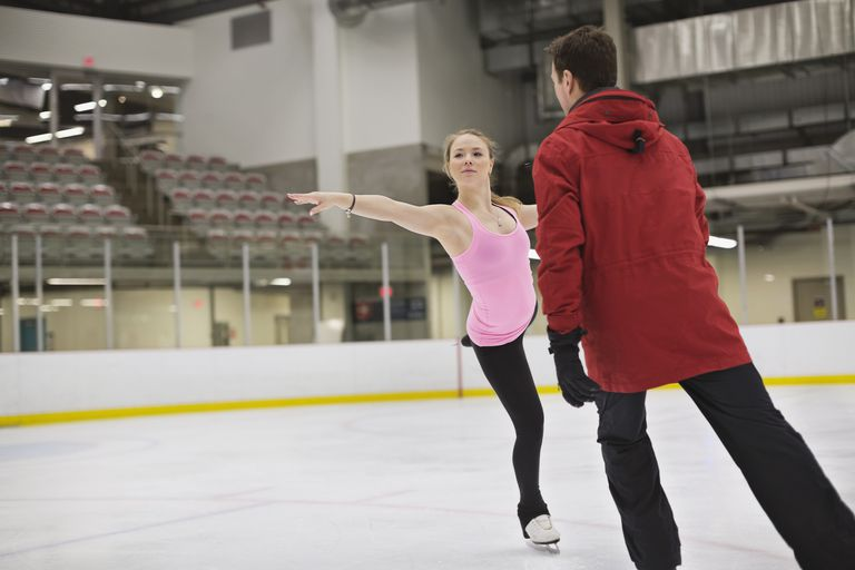 An ice skating coach training a young athlete