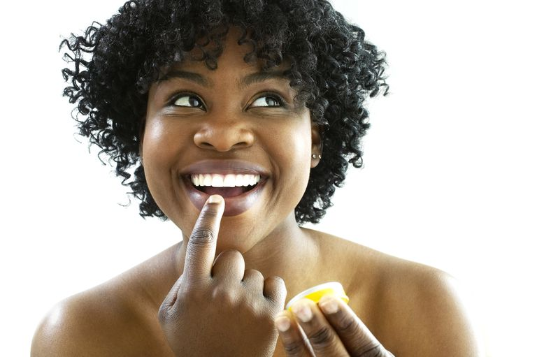 Woman putting on lip balm.