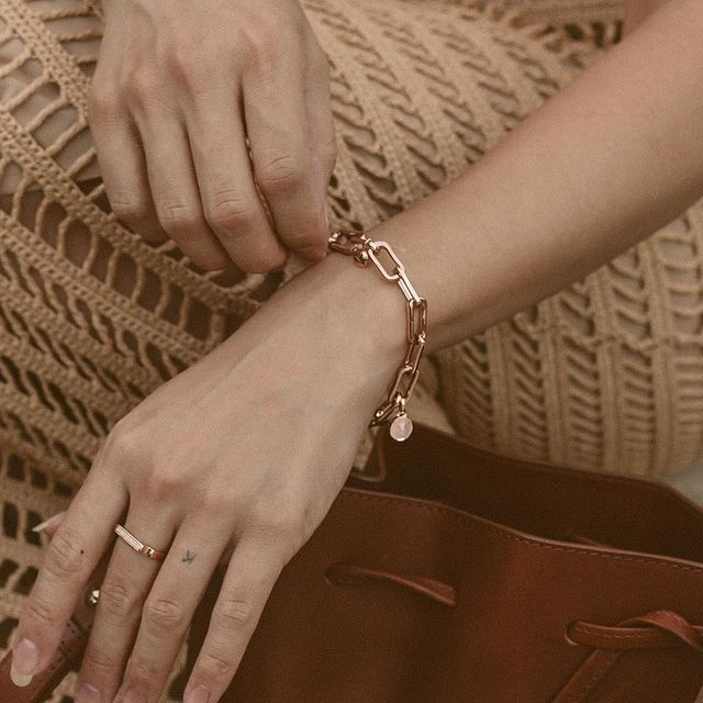 Close-up of rose gold chain link bracelet and ring
