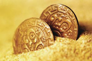 Two ancient coins, partially buried in sand