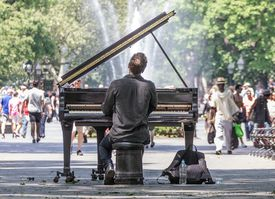 Man playing piano in a busy city park