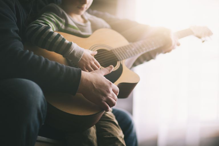Father playing guitar with son