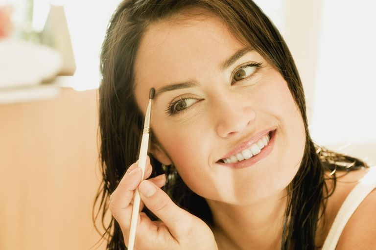 Close-up of a mid adult woman brushing her eyebrows