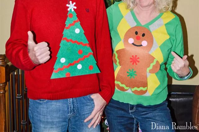 A couple wearing ugly Christmas sweaters in front of a Christmas tree