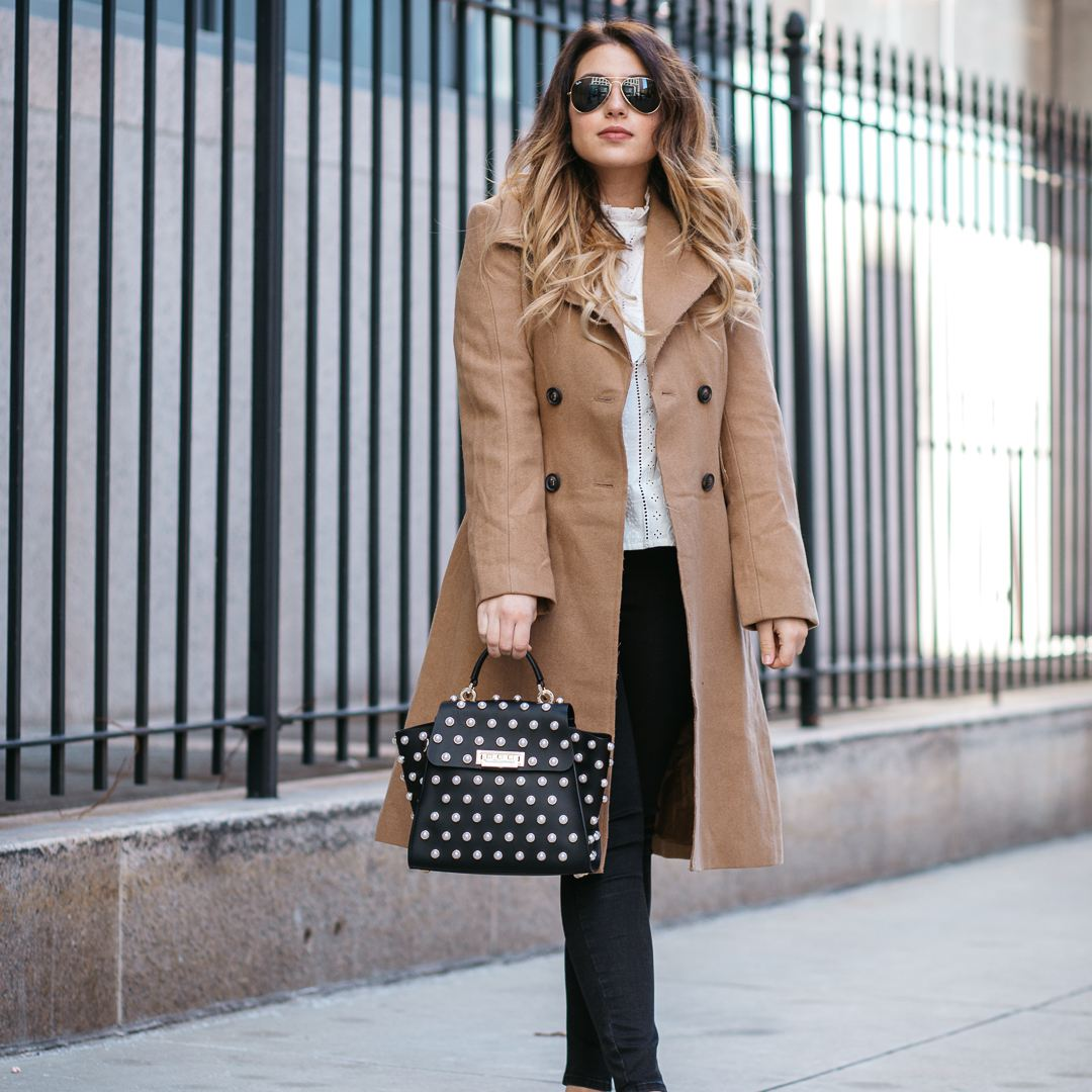 woman in trench coat and jeans with polka dot purse