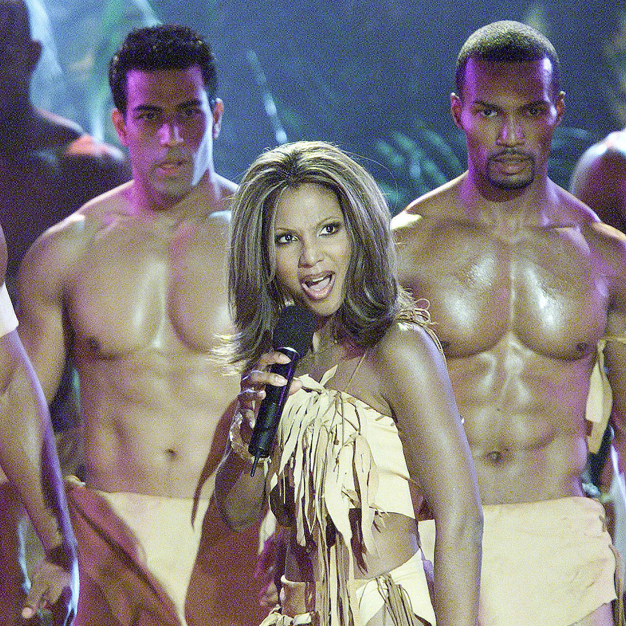 Toni Braxton performing in front of muscular, shirtless men