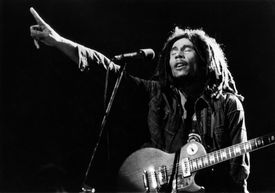 Bob Marley pointing up and singing during performance with guitar