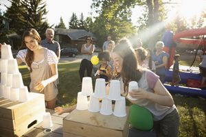 Teenage girls play cup stacking game at summer neighborhood block party in sunny park