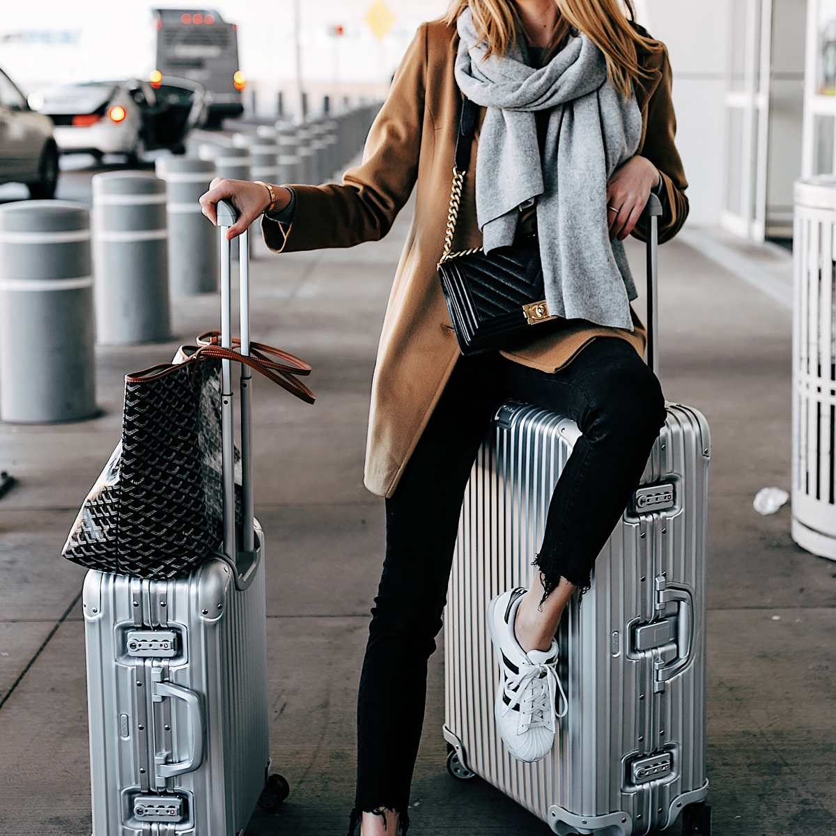 Woman in chic airport outfit with luggage
