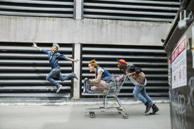 Playful cool young friends pushing shopping cart in urban alley