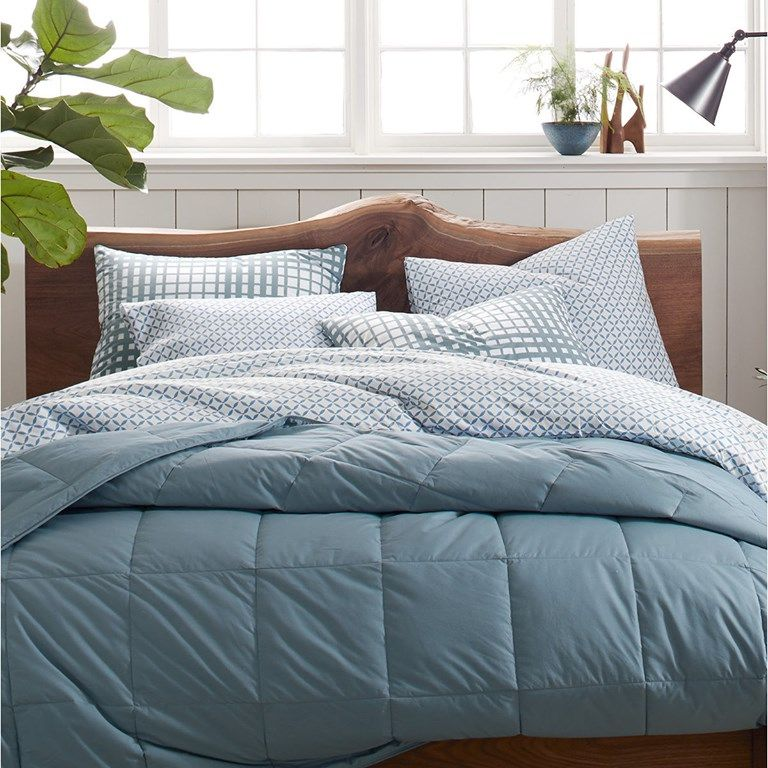 A wooden bed with blue blankets from Garnet Hill