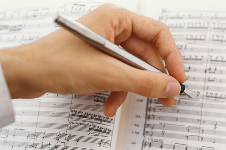 Hand holding pen writing music