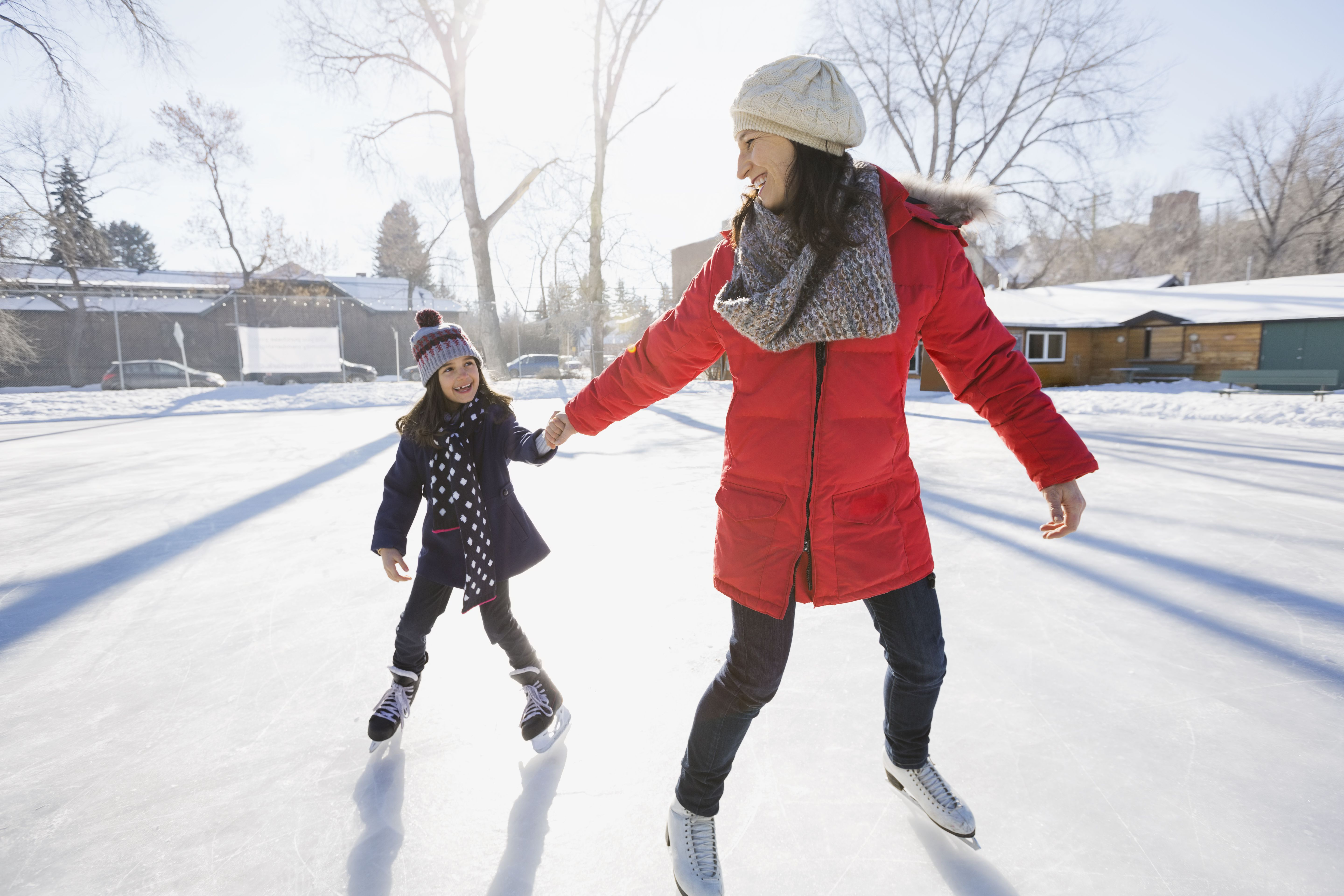learn how to ice skate in  steps mother and daughter ice skating on rink