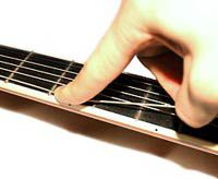 While one hand tightens the tuner, the other hand creates tension in the string.